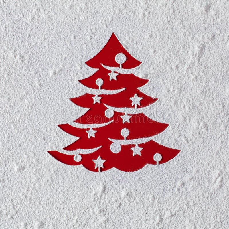 Carte de Noël avec le dessin d'arbre de Noël en farine sur le rouge image stock