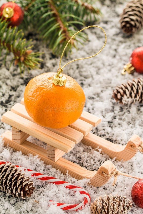Carte de Noël avec le traîneau en bois, avec le tangerin frais photo stock