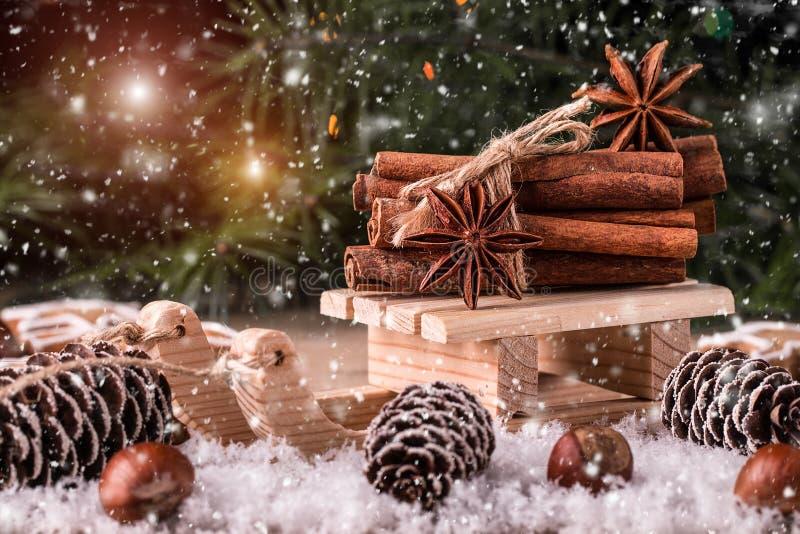 Carte de Noël avec le traîneau en bois avec le tas de la cannelle photographie stock