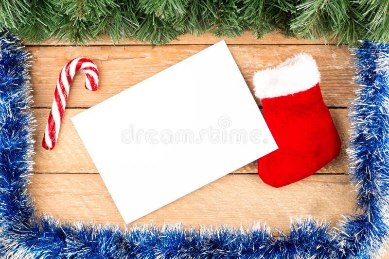 Carte de Noël, branches d'arbre, papier, botte, crochet de sucrerie avec le fram photos stock