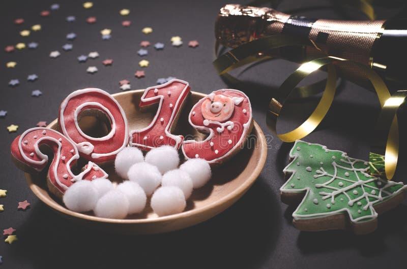 Carte de Noël : d'un plat en bois sont les biscuits de gingembre rouge sous forme de numéros 2019 et flocons de neige ronds blanc photo libre de droits