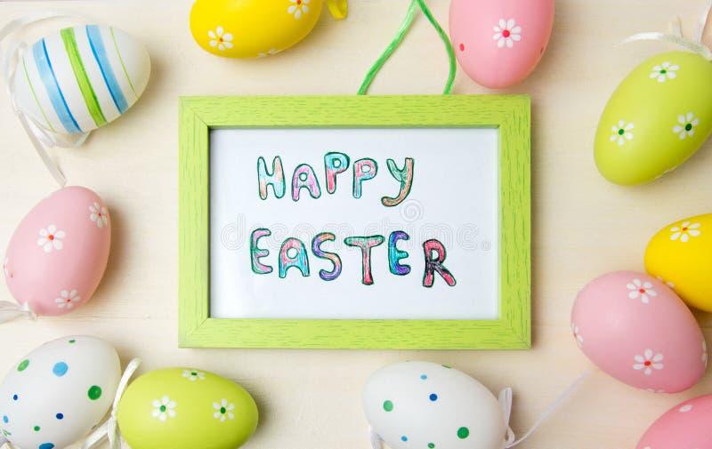 Carte de Pâques heureuse dans un cadre avec les oeufs colorés photos stock