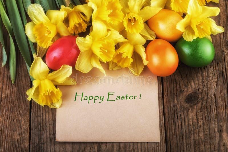 Carte de Pâques heureuse - le jaune fleurit l'effet de lumière du soleil photo stock
