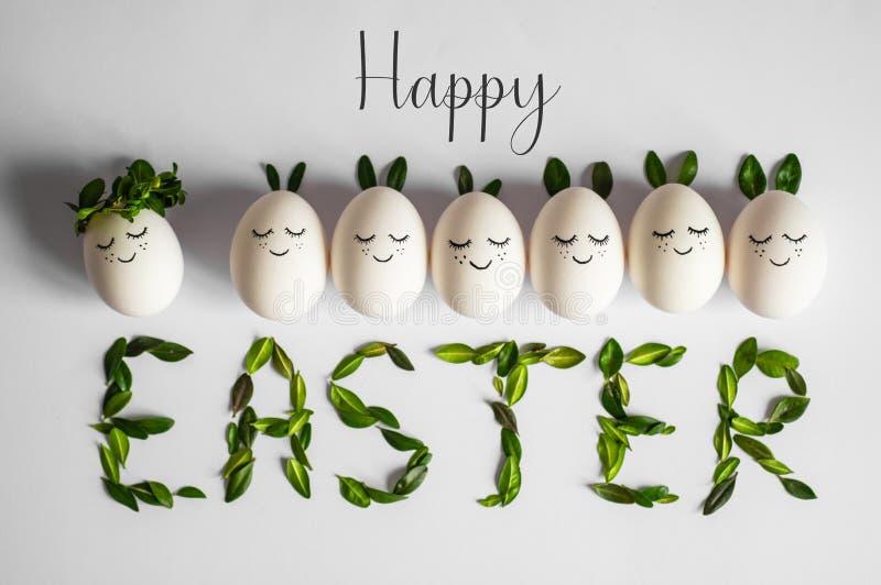 Carte de Pâques heureuse Oeufs de pâques mignons avec un visage peint dans une guirlande de ressort avec l'espace de copie pour l photographie stock libre de droits