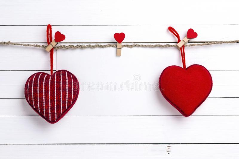Carte de papier blanc avec les coeurs rouges accrochant sur des pinces à linge sur le fond en bois blanc L'espace pour le texte images stock