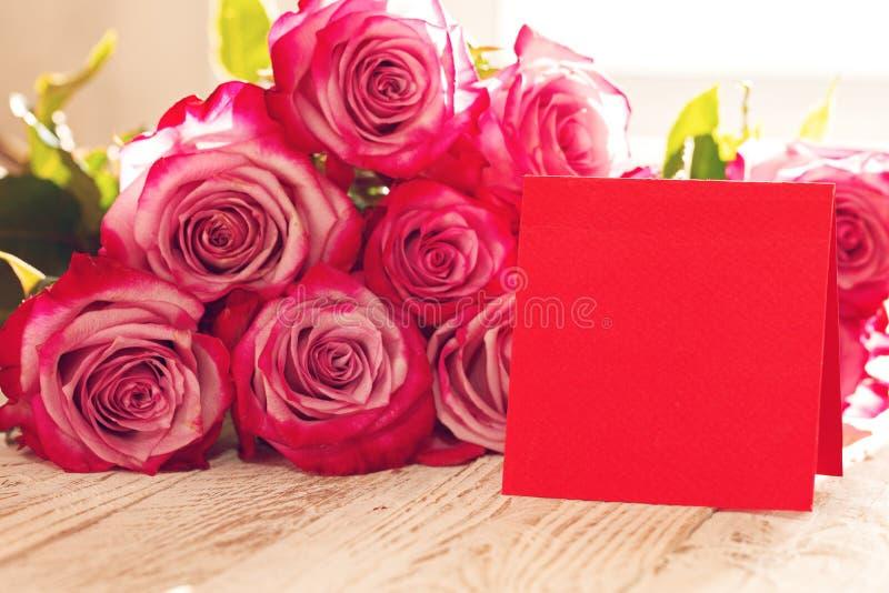 Carte de papier rouge vierge pour des valentines ou le jour de mère ou de femme Fond avec les roses roses photo stock