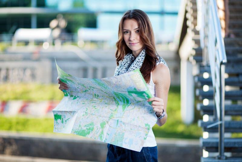 Carte de papier se tenante de touristes de jeune femme dehors photos libres de droits
