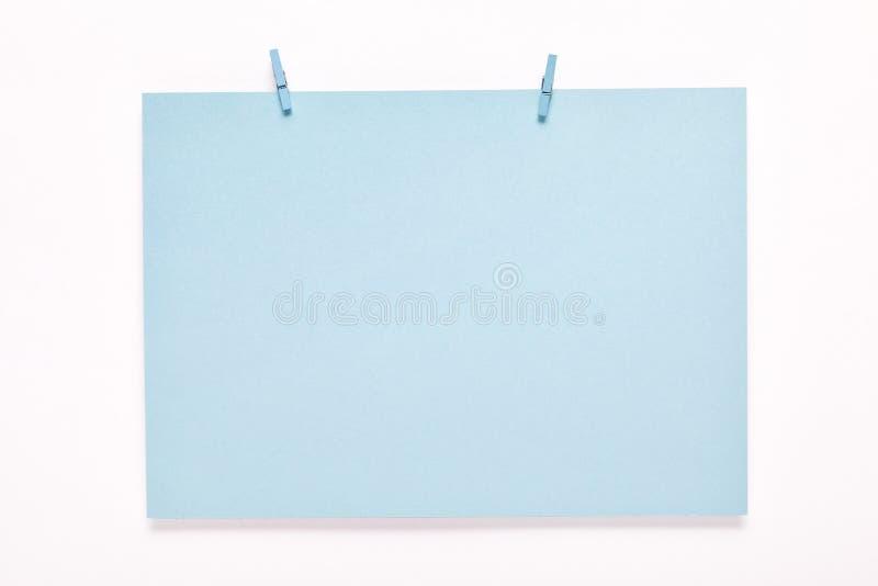 Carte de papier sur la pince à linge sur le fond blanc image stock