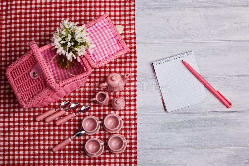 Carte de pique-nique avec l'arrangement de table et les perce-neige, argenterie, serviette vérifiée blanche rouge photographie stock