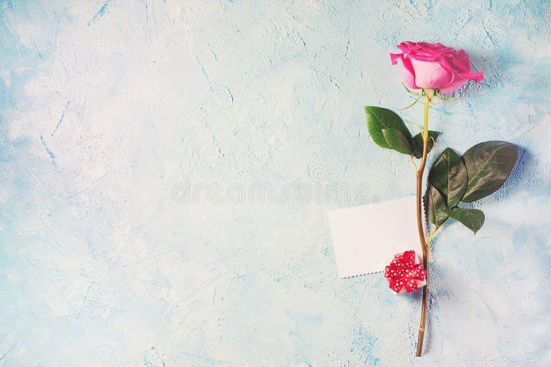 Carte de Saint Valentin - on rose s'est levé avec le cadeau et la note sur le te bleu images stock