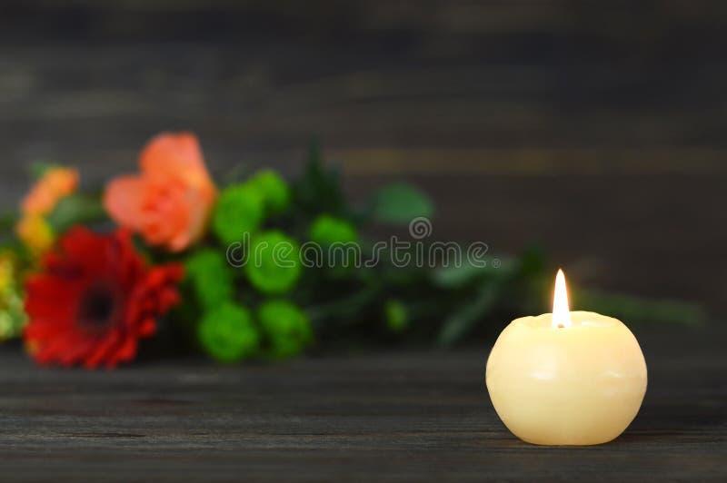 Carte de sympathie avec la bougie et les fleurs commémoratives photographie stock