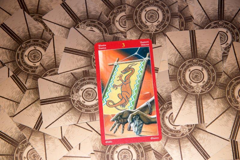 Carte de tarot trois des baguettes magiques Plate-forme de tarot de dragon Fond ésotérique photos stock