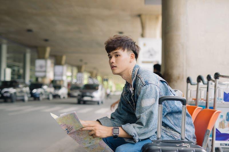 Carte de touristes masculine asiatique de lecture tout en attendant le taxi sur le sto d'autobus photographie stock libre de droits