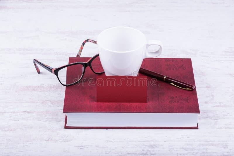 Carte de visite professionnelle rouge vierge de visite et maquette blanche de tasse Livre, stylo et verres rouges sur le fond en  images stock