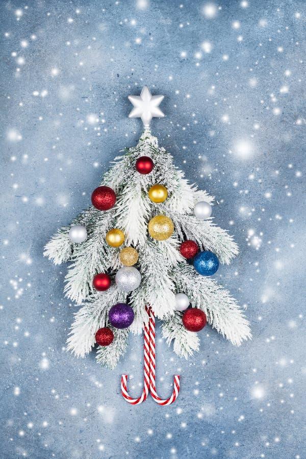 Carte de voeux avec l'étoile décorée créative d'arbre de sapin de Noël et boules colorées sur la vue supérieure de fond bleu Effe photos stock