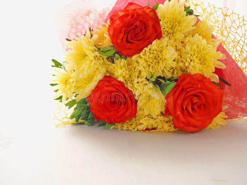 Carte de voeux avec le chrysanthème jaune et roses rouges dans le coin supérieur droit Carte de voeux photos stock