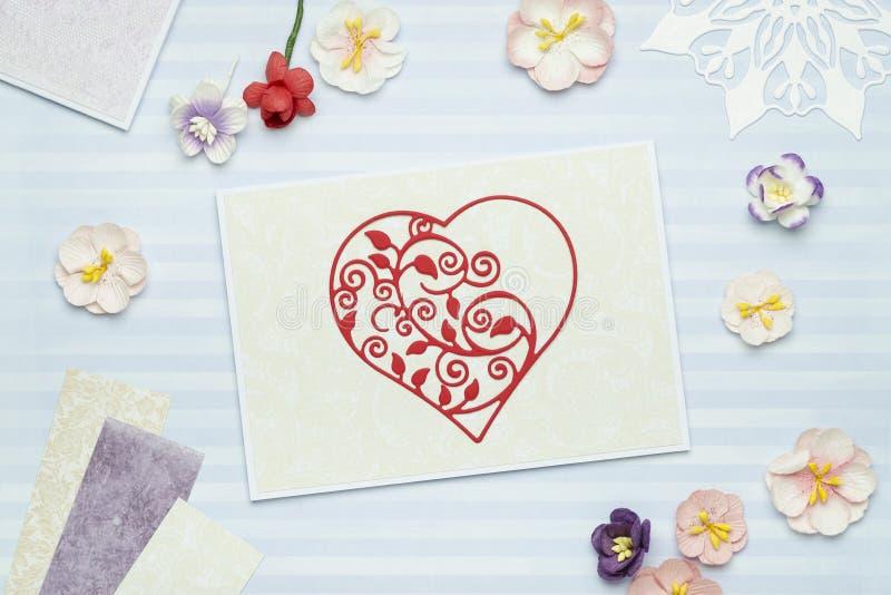 Carte de voeux avec le coeur rouge fait de papier sur le fond bleu avec les fleurs de papier images libres de droits