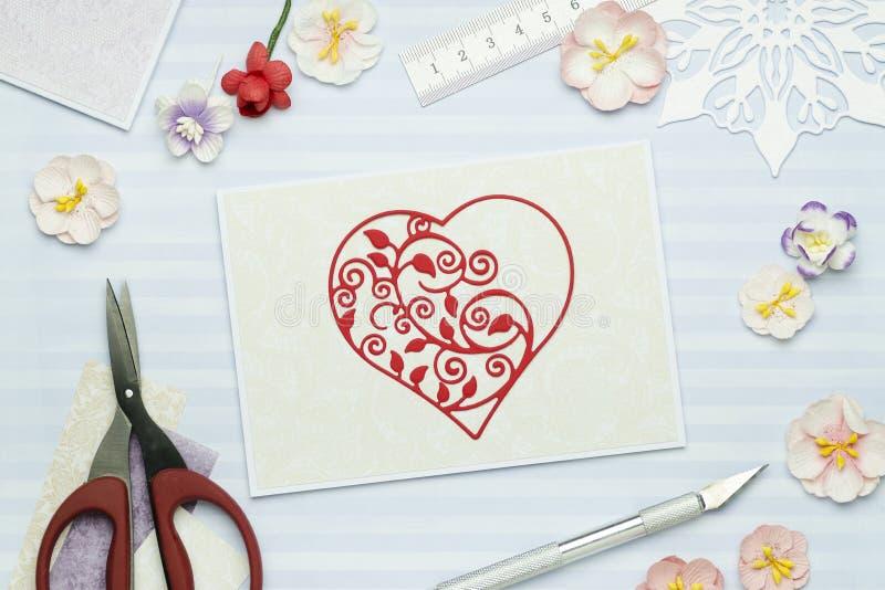 Carte de voeux avec le coeur rouge fait de papier sur le fond bleu avec les fleurs de papier photos stock
