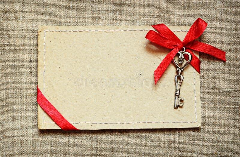 Carte de voeux avec le ruban rouge et une clé images libres de droits