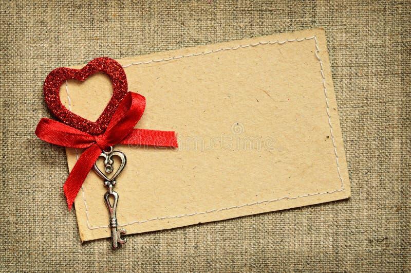 Carte de voeux avec le ruban rouge et une clé pour la Saint-Valentin photo stock