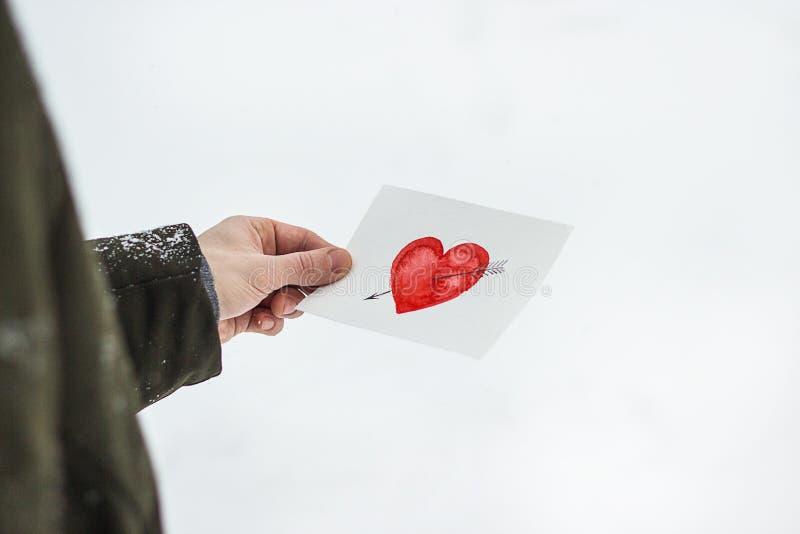 carte de voeux avec un coeur peint rouge dans les mains, une déclaration de l'amour la Saint-Valentin photographie stock