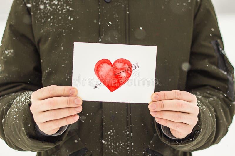 carte de voeux avec un coeur peint rouge dans les mains, une déclaration de l'amour la Saint-Valentin photos libres de droits