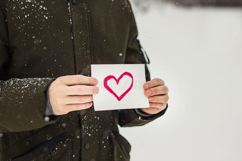 carte de voeux avec un coeur peint rouge dans les mains, une déclaration de l'amour la Saint-Valentin images stock