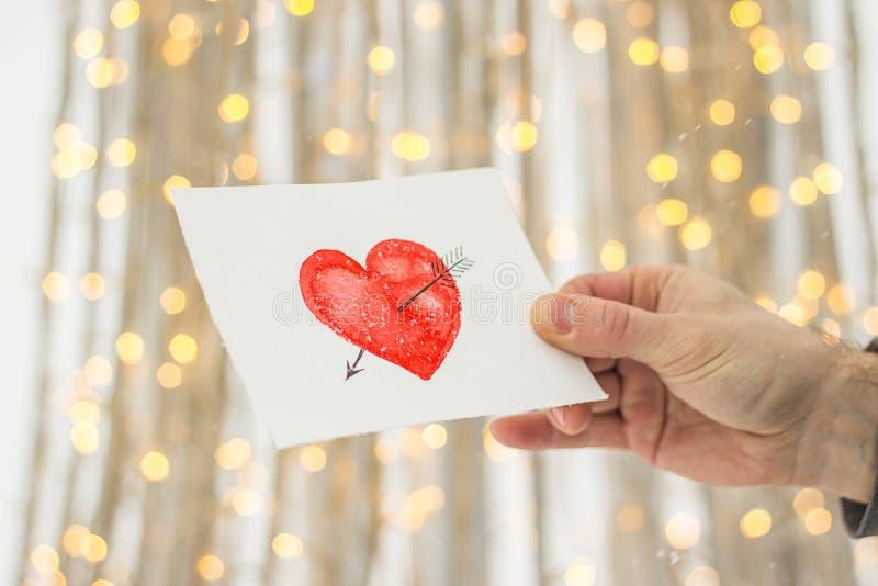 carte de voeux avec un coeur peint rouge dans les mains, une déclaration de l'amour la Saint-Valentin photo libre de droits