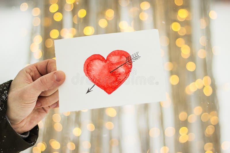 carte de voeux avec un coeur peint rouge dans les mains, une déclaration de l'amour la Saint-Valentin images libres de droits