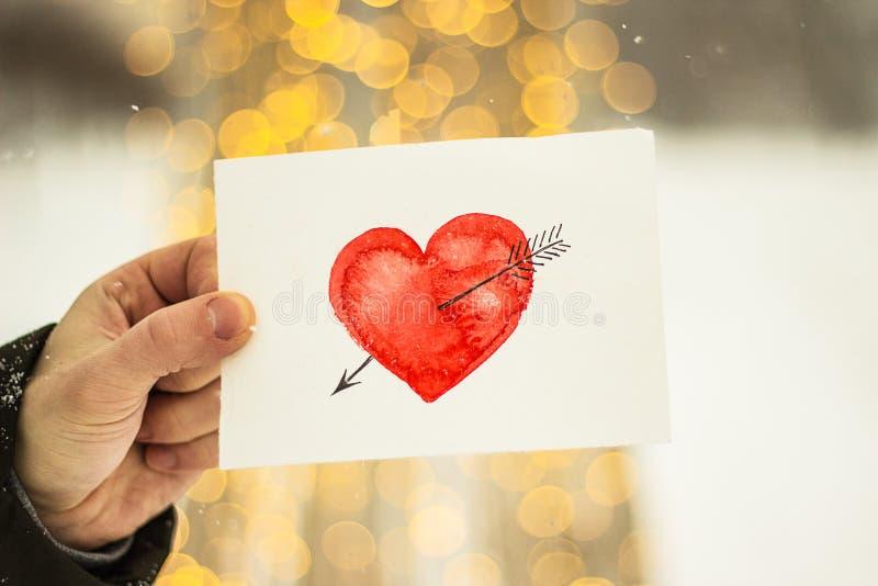 carte de voeux avec un coeur peint rouge dans les mains, une déclaration de l'amour la Saint-Valentin photo stock
