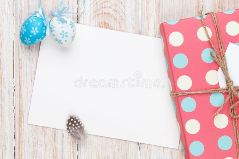 Carte de voeux de Pâques avec les oeufs bleus et blancs et le boîte-cadeau plus de image stock