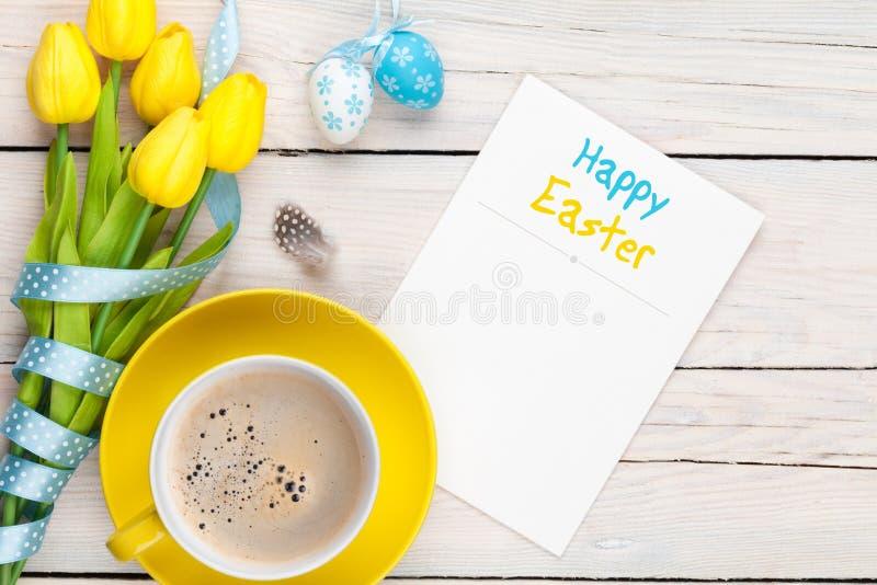 Carte de voeux de Pâques avec les oeufs bleus et blancs, tulipes jaunes et photographie stock