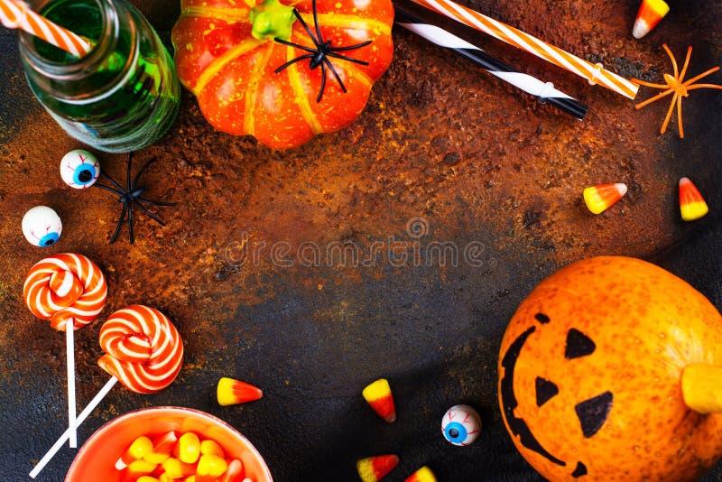 Carte de voeux de Halloween - boissons, sucreries et décor sur le fond foncé photo libre de droits