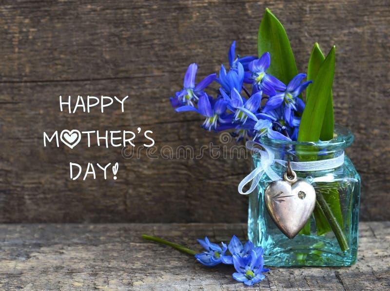 Carte de voeux heureuse du jour de m?re avec les fleurs bleues de ressort de siberica de Scilla dans un vase en verre avec le coe photographie stock libre de droits