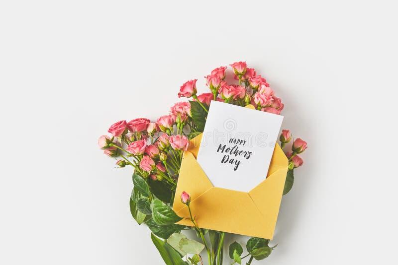 carte de voeux heureuse de jour de mères dans l'enveloppe et belles roses roses sur le gris photo stock