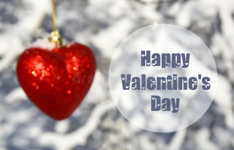 Carte de voeux heureuse de Saint-Valentin avec le coeur rouge décoratif brouillé sur le fond neigeux blanc d'arbres le 14ème févr photo libre de droits