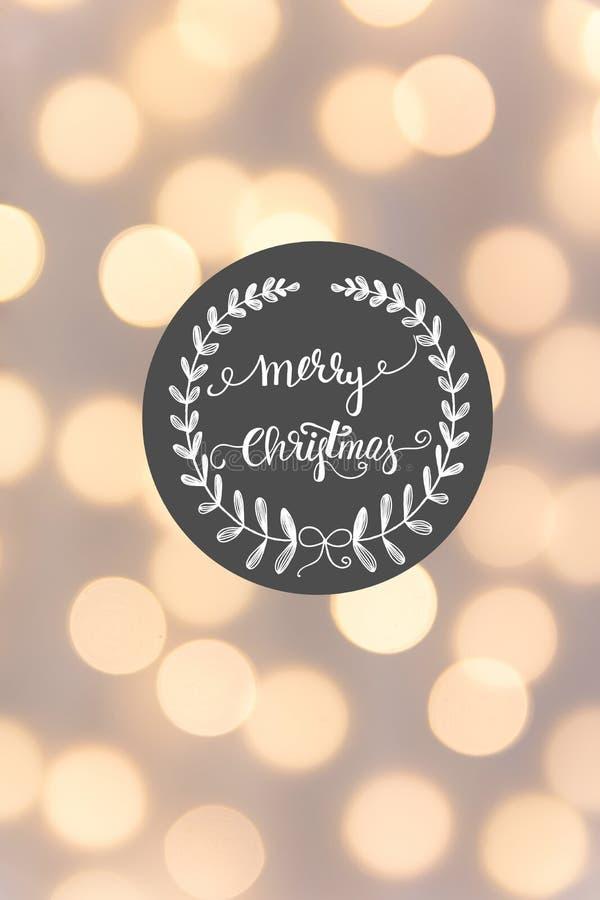 Carte de voeux de Joyeux Noël E Lumières d'or de bokeh de guirlande Lettrage unique de main images stock