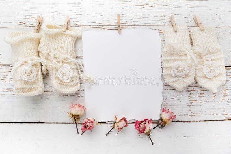Carte de voeux nouveau-née ou de baptême Blanc avec des chaussures et des gants de bébé sur le fond en bois blanc photos libres de droits