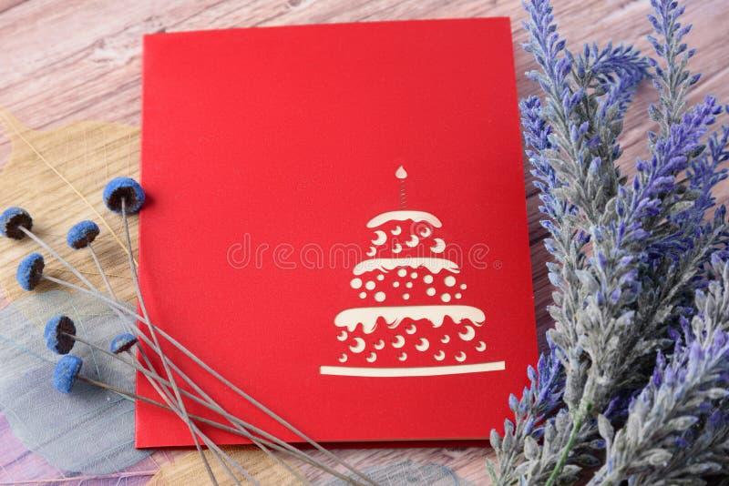Carte de voeux rouge avec l'endroit pour le texte et les fleurs sur un fond en bois clair photos stock