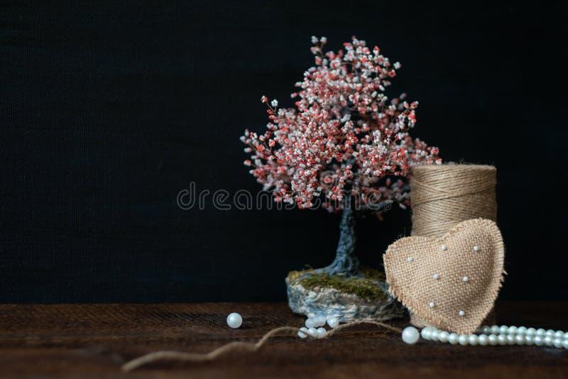 Carte de voeux rustique de jour de valentines, fond Coeur fait main de toile de jute avec des perles, des perles, la bobine de la photographie stock