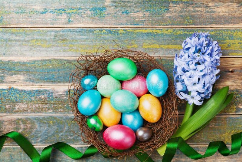 Carte de voeux sur Pâques des fleurs et du nid avec les oeufs colorés sur la vue supérieure en bois rustique de table Vacances tr image libre de droits