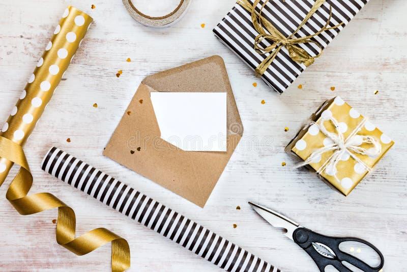 Carte de voeux vierge en enveloppe de métier, boîte-cadeau et matériaux d'emballage sur un fond en bois blanc image stock
