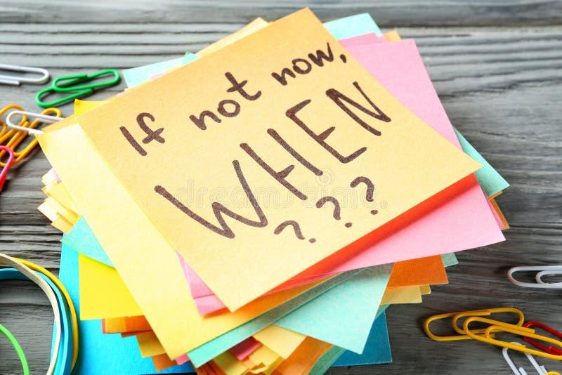 Carte dell'autoadesivo con la frase ispiratrice se non ora, QUANDO??? sulla tavola di legno fotografia stock