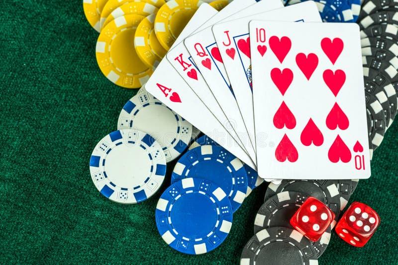 Carte della mazza dei dadi e chip rossi di gioco dei soldi fotografia stock