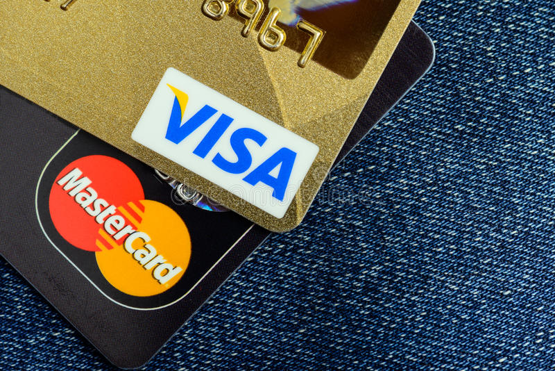 Carte di credito di Mastercard e di visto sopra le blue jeans immagine stock