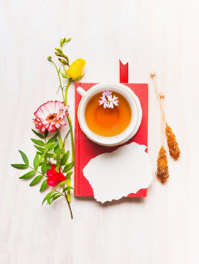 Carte di festa della Mamma di concetto, vari fiori, presentati intorno al libro e ad una tazza di tè, posto per testo fotografia stock libera da diritti