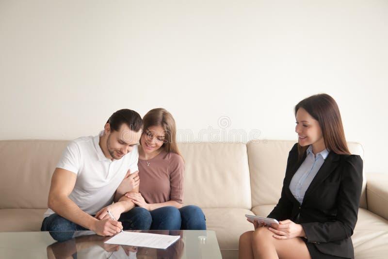 Carte di firma del giovane che si siedono accanto alla moglie ed all'agente immobiliare immagine stock libera da diritti