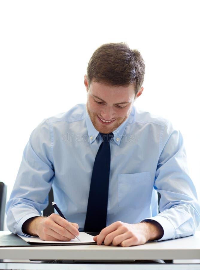 Carte di firma sorridenti dell'uomo d'affari in ufficio immagine stock libera da diritti