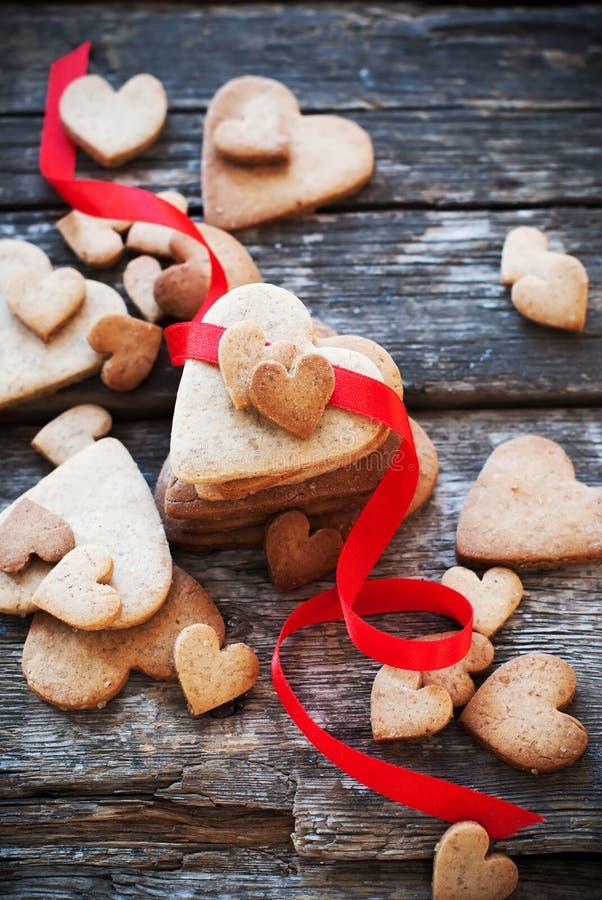 Carte di San Valentino dei biscotti con la fila rossa sulla Tabella di legno immagini stock libere da diritti