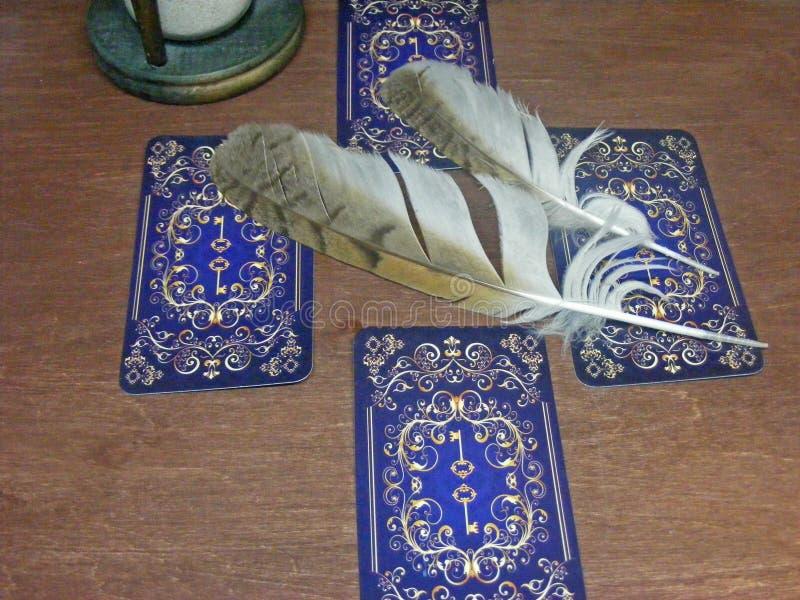 Carte di tarocchi con le piume del gufo e clessidra su fondo marrone fotografie stock libere da diritti